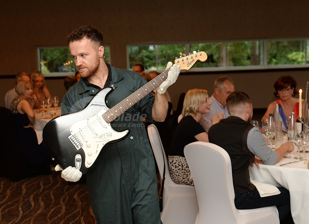 Man showing a guitar at a Antiques Auction Corporate Event