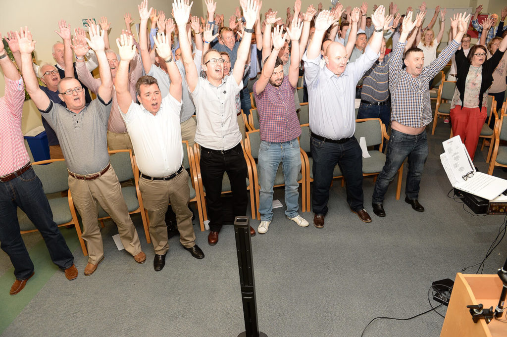 Men standing up smiling hands in the air for Body percussion conference ice breaker