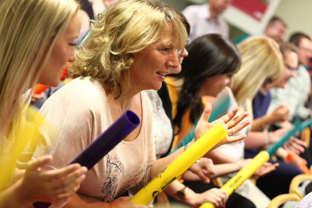 Women using boomwhackers at a conference ice breaker