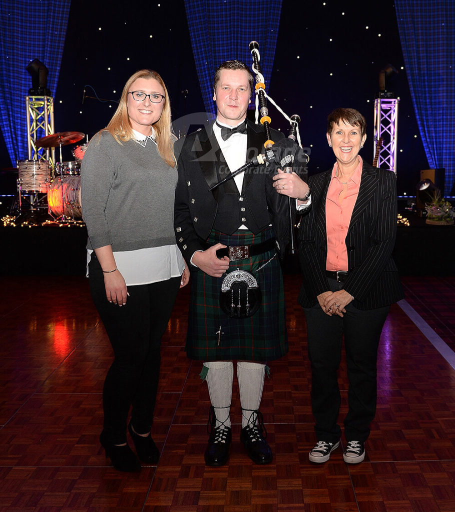 People posing with a bagpiper at a Scottish themed corporate event