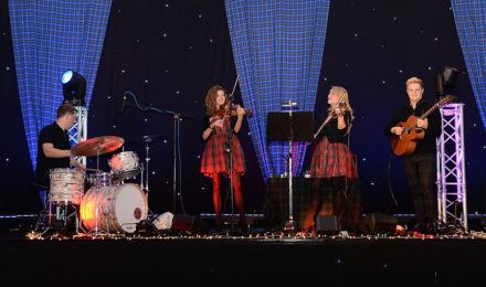 Scottish girls in a band playing at a Scottish themed company party