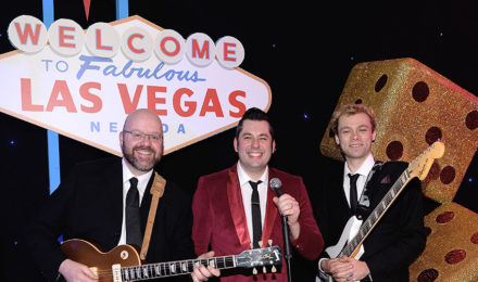 Rock n Roll band in front of a Las Vegas sign at a corporate event