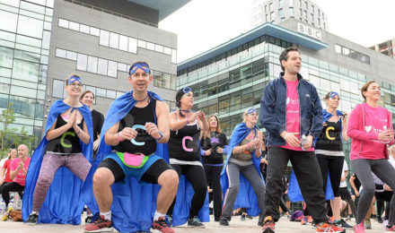 Team in capes warming up by BBC building for It's a Knockout team build