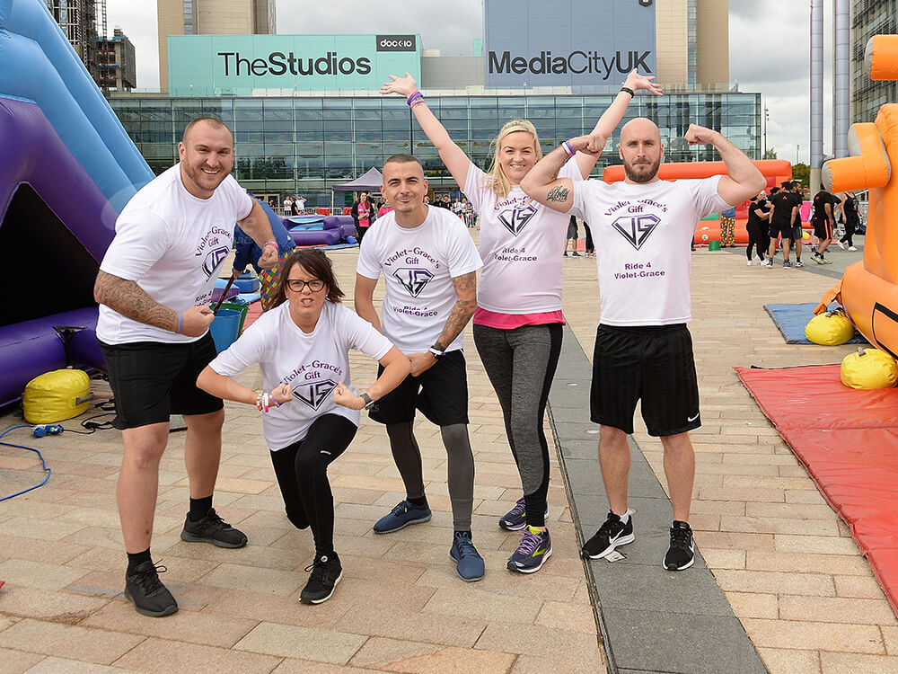 Team in white t shirts posing at Media City UK taking part in It's a Knockout team event