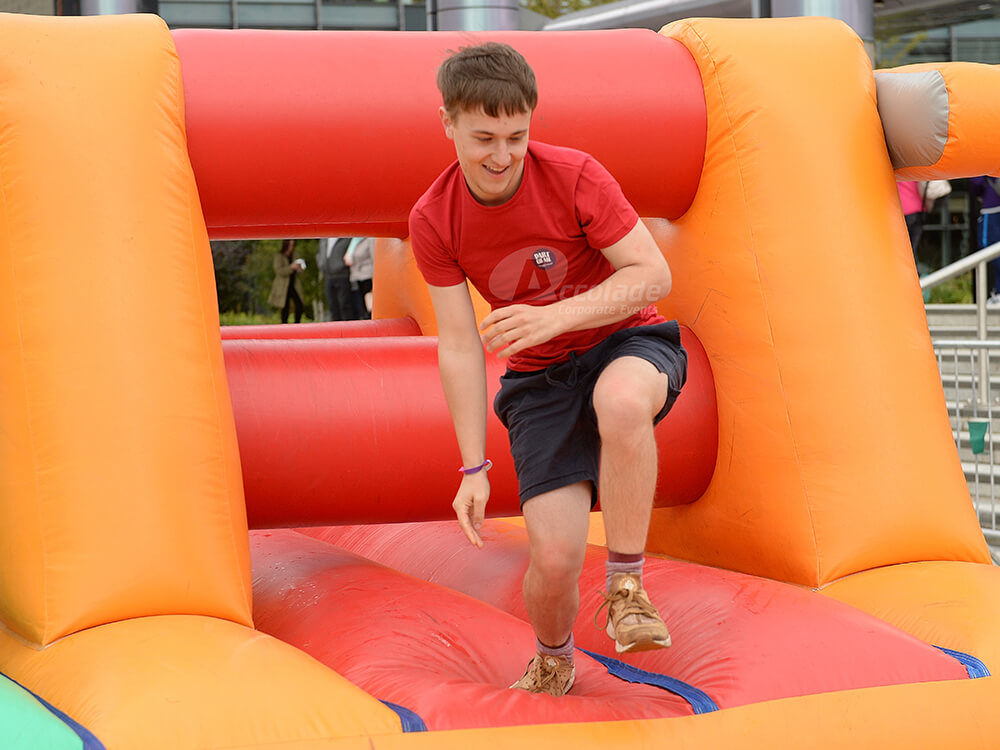 Man climbing through inflatable its a knockout total wipe out event
