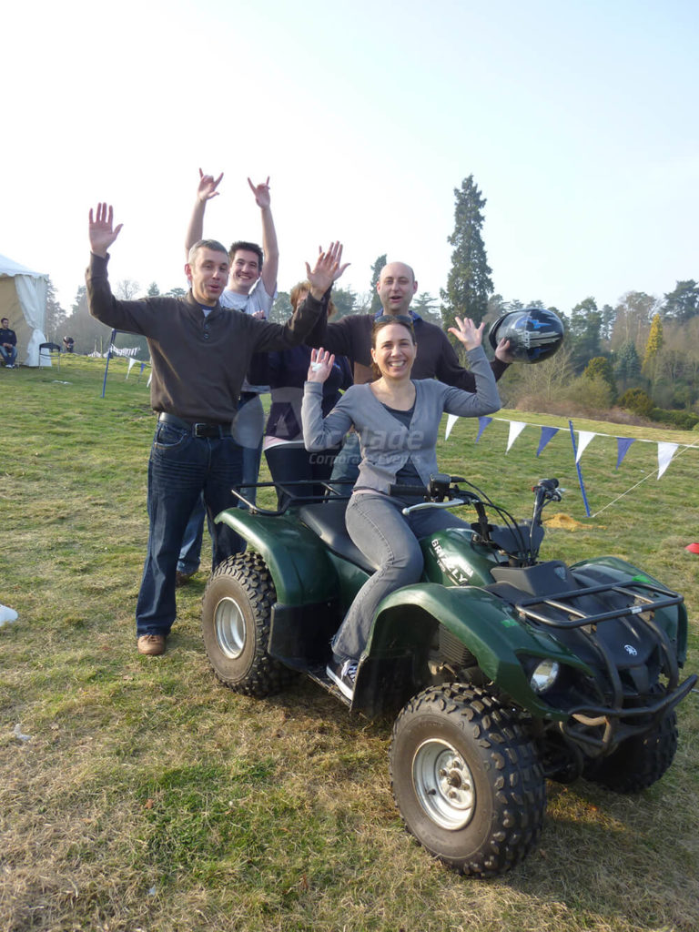 Happy team on a quad bike at company away day