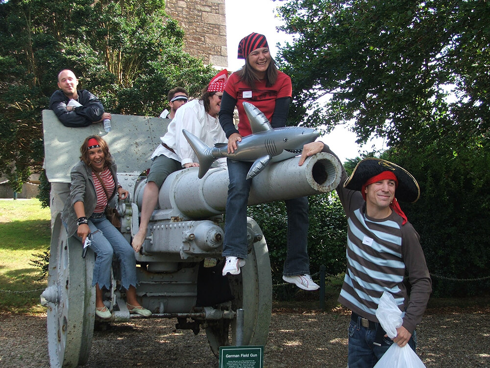 Team dressed as pirates sitting on a canon in Spy Catcher team building event