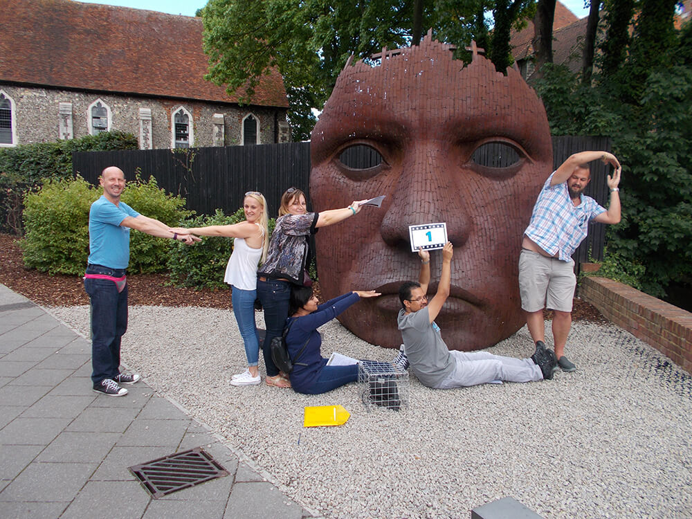 Team spelling help in front of giant mask in Spy Catcher team building event