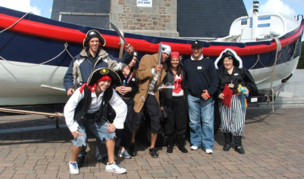 Pirate team posing by lifeboat in Spy Catcher corporate event