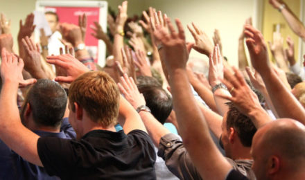 Conference ice breaker with people with hands in the air