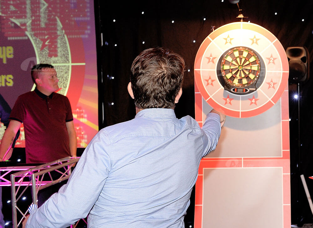 Man throwing darts at company party event