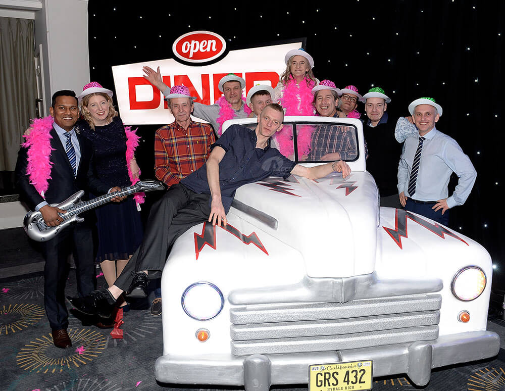 People posing around Cadillac car at company event