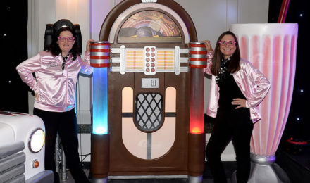 Women standing by giant jukebox prop at American diner themed party