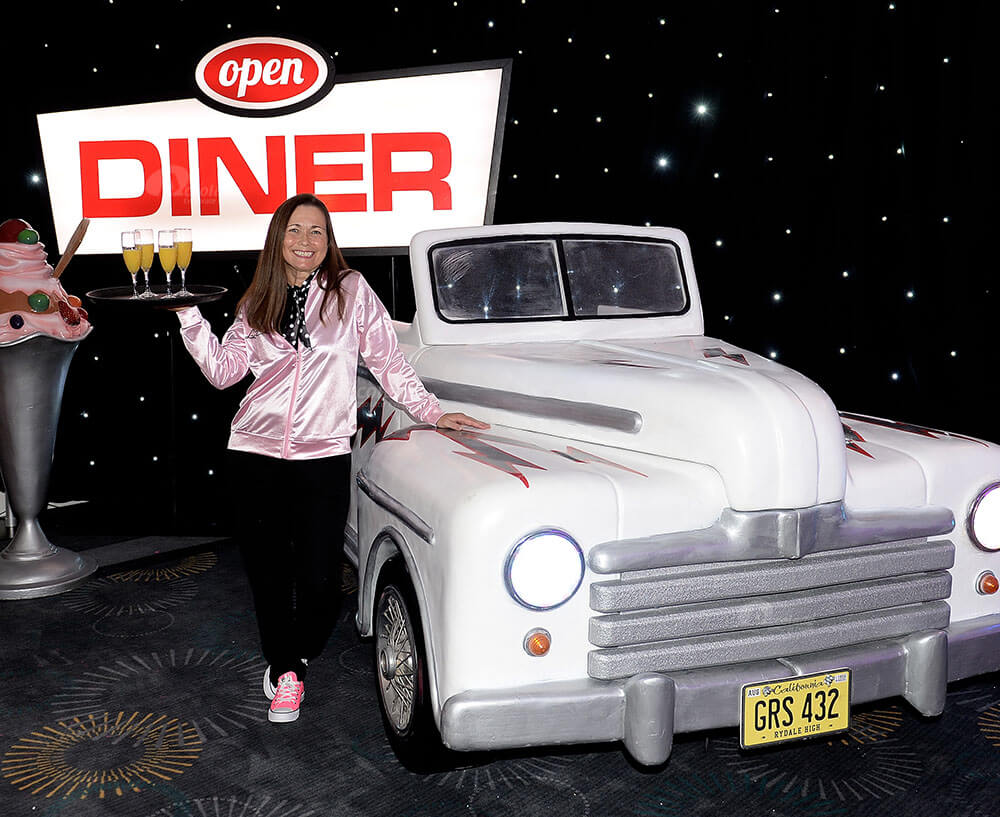 Waitress posing by Cadillac car and diner sign at themed American diner party