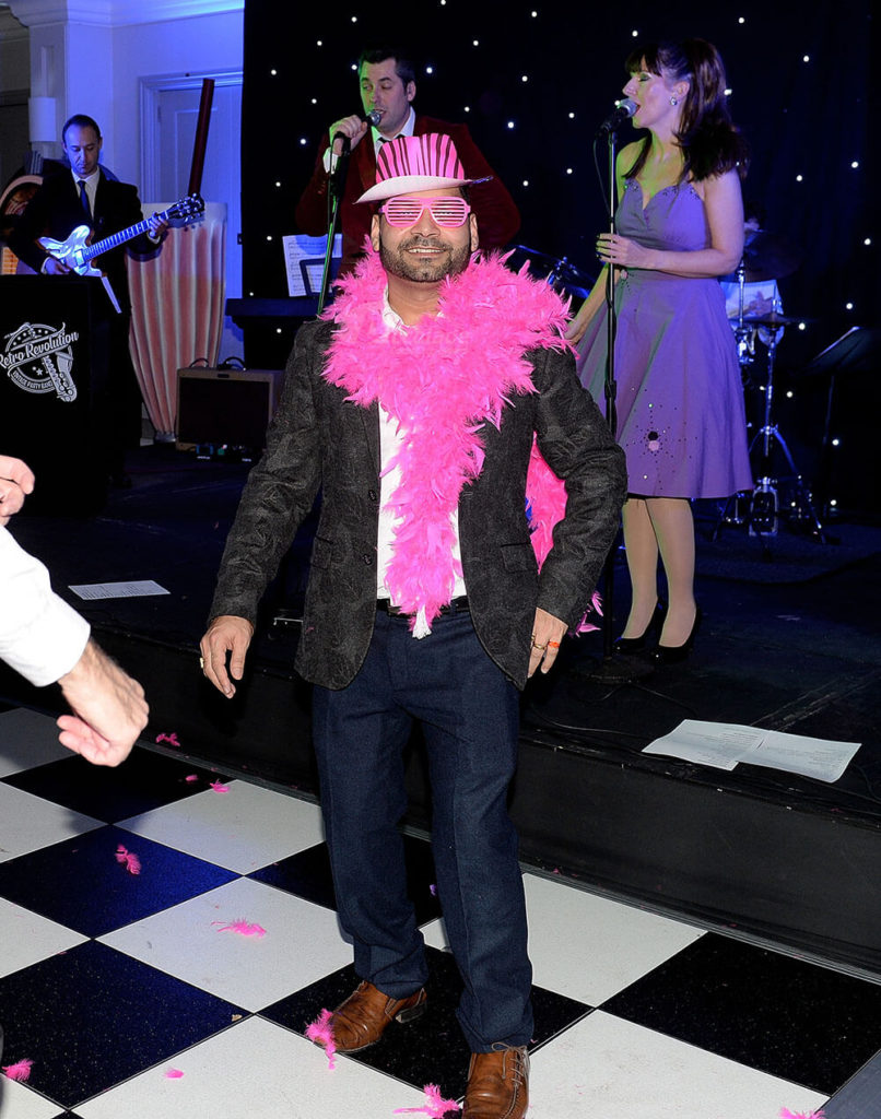 man smiling on chequered dance floor at annual company party