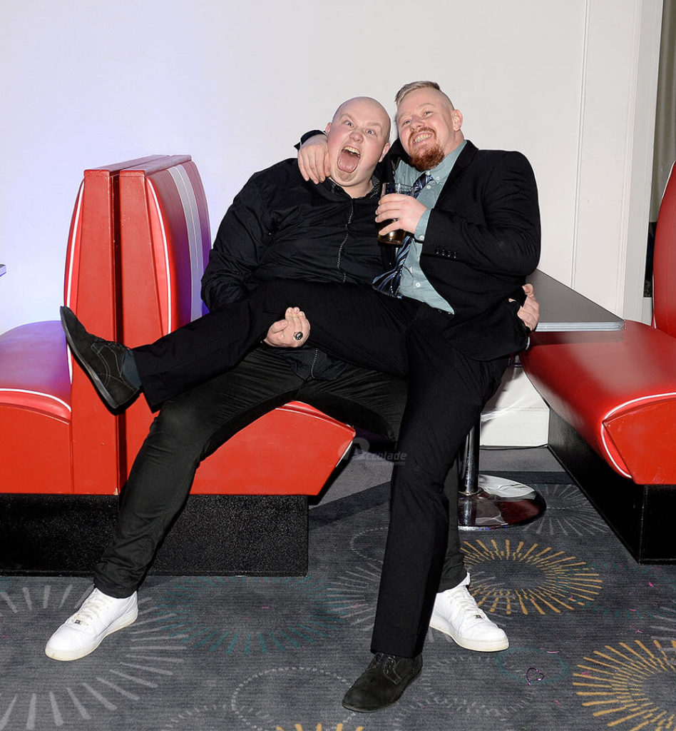 Two men in a diner booth at themed party