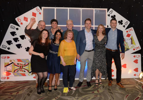 Team in front of giant card wall at Play your cards